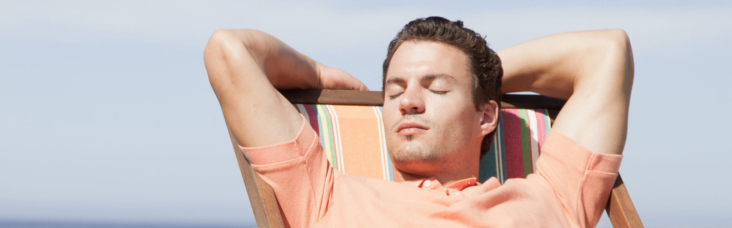 man relaxing with eyes closed in a beach chair