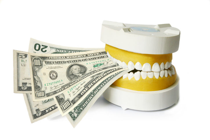 Dental implant cost - Fake teeth biting down on money on a white background