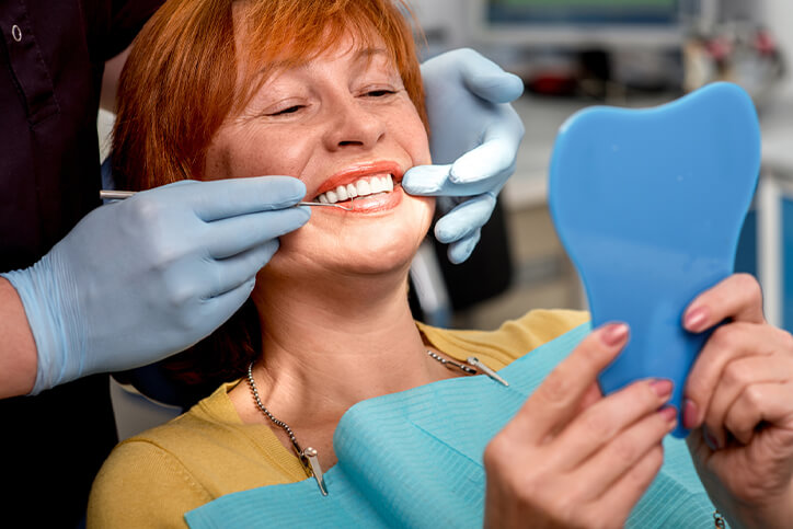 older woman smiling in dentist's chair
