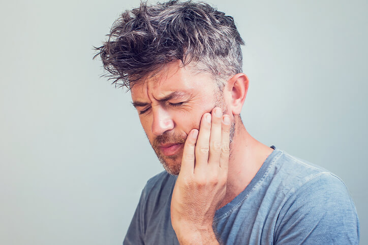 Man in blue shirt holding his mouth in pain