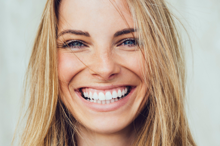 A young woman smiling after she received veneers