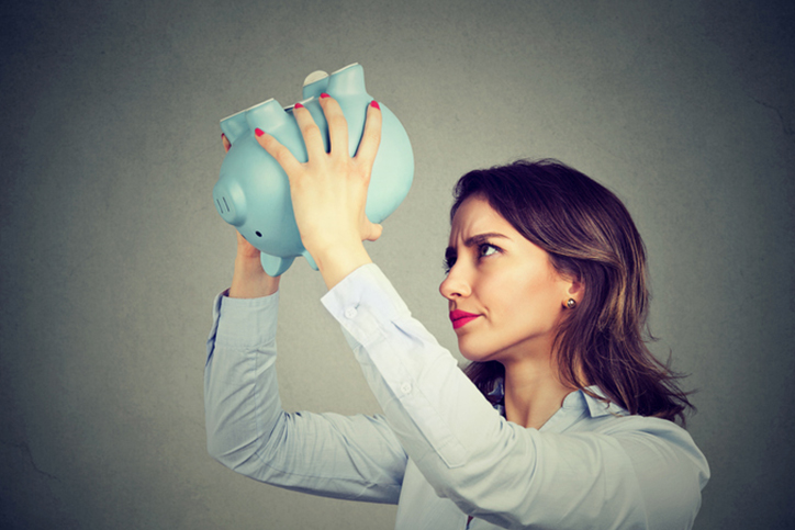A woman looking in a piggy bank for money