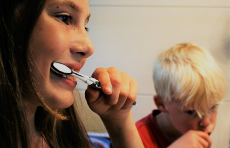 young boy and girl brushing their teeth