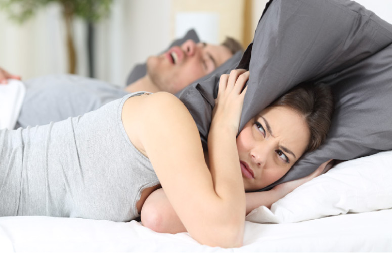 woman covering her ears with a pillow to block out her partners snoring from sleep apnea